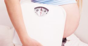 a pregnant woman holding a scale to symbolize weight gain in pregnancy